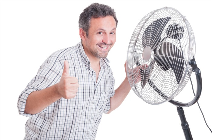 man in front of a fan. Central air conditioning tips