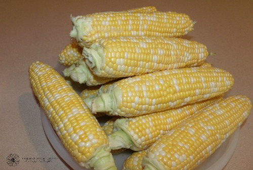 a piles of corn ears ready for freezer corn recipe