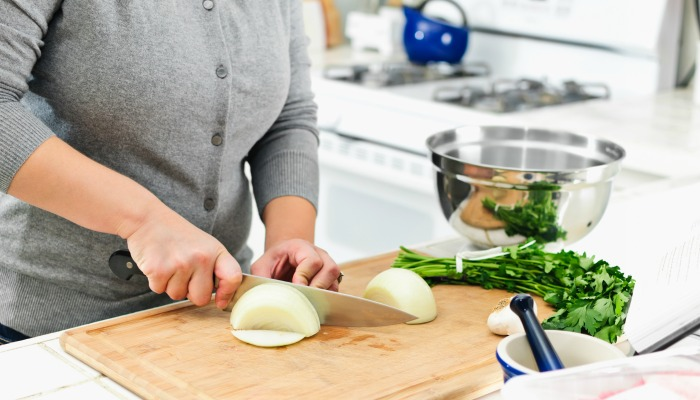 A woman chopping an onion. How to have a stress free Thanksgiving dinner