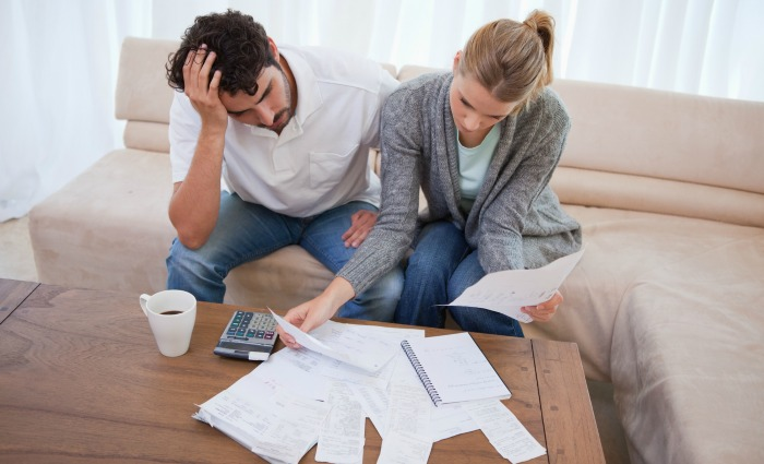 Couple worried about money. Learn saving money with these thrifty money saving tips