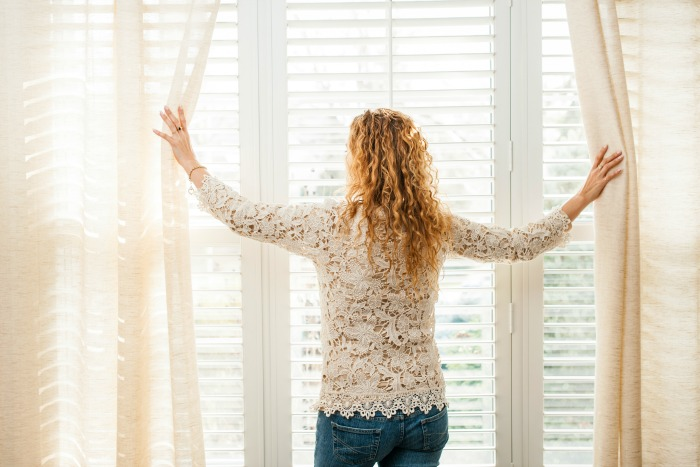 A woman looking out the window.How to get more done, productivity tips that will help you get more done in less time. #productivity #getmoredone #timemanagement