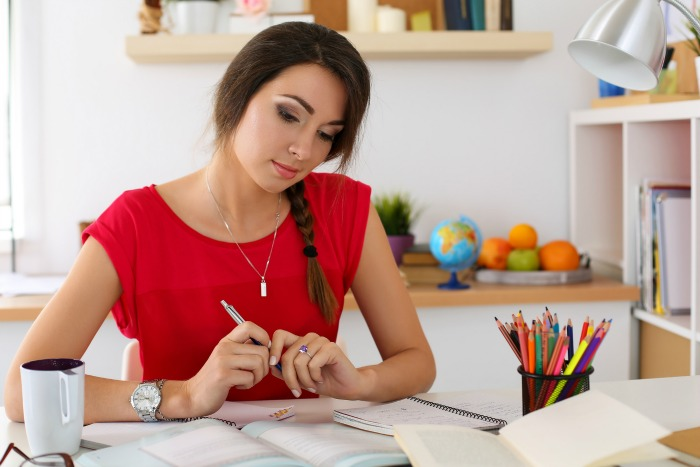 A woman doing homework. How to get more done, productivity tips that will help you get more done in less time. #productivity #getmoredone #timemanagement