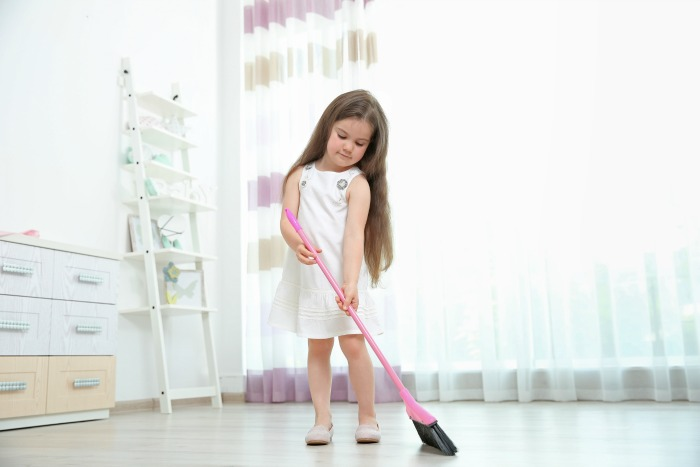 Young girl sweeping the floor.How to keep a clean house in under 20 minutes a day.