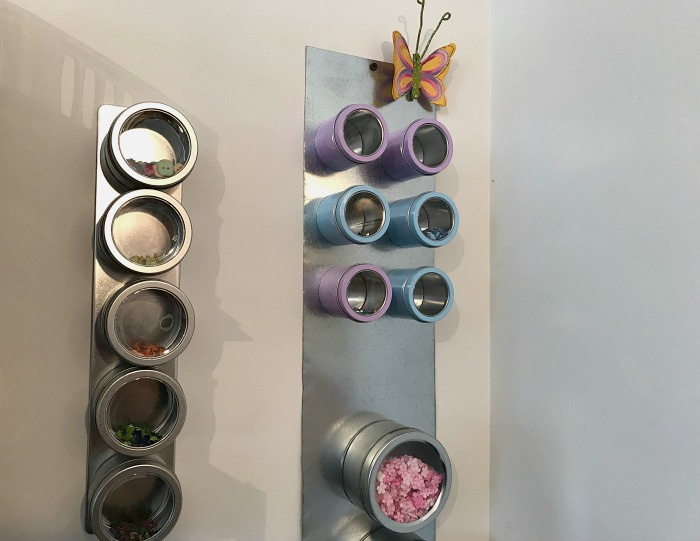 magnetic organizer on a wall holding misc craft supplies.