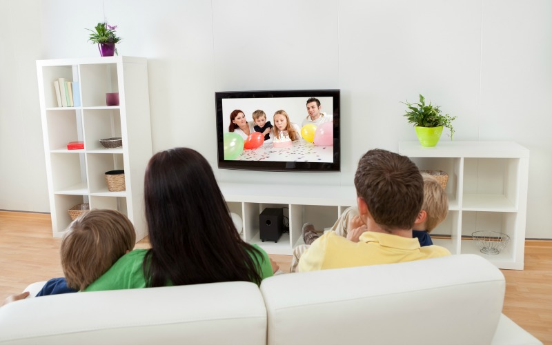 Young happy family watching TV at home. how to declutter your family room