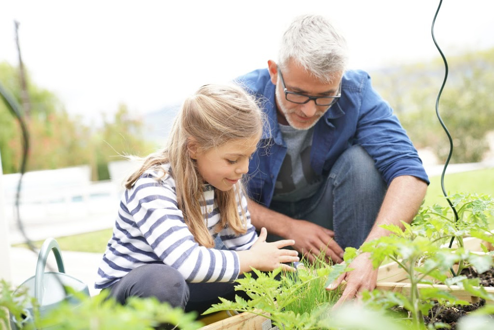 A father and daughter learn about plants in a family garden