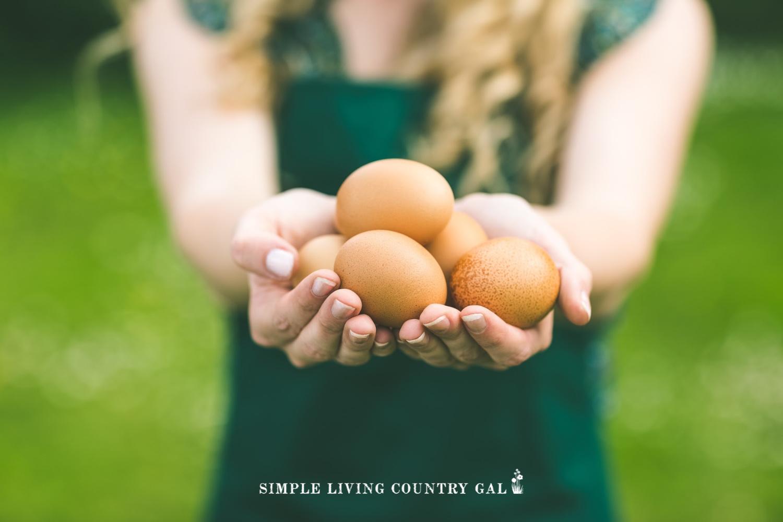 a woman holding backyard chicken eggs