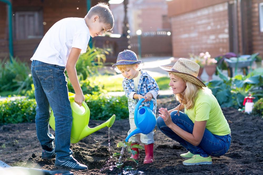 kids watering vegetables in a baby food garden