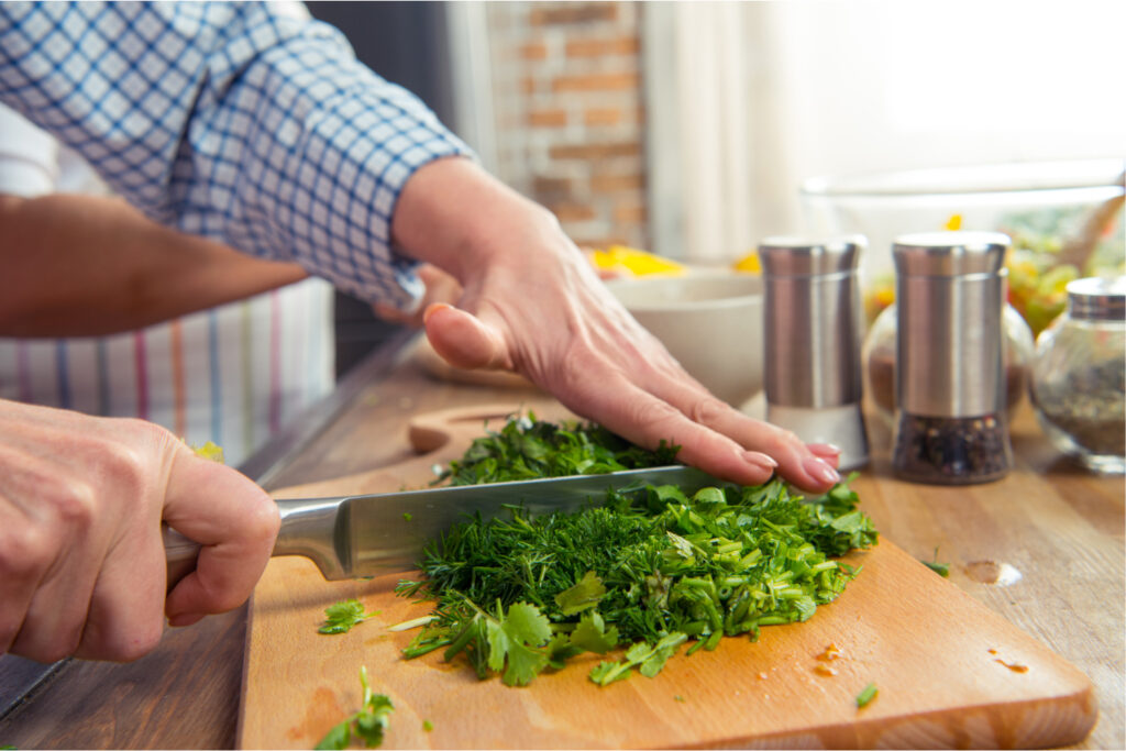 chopping fresh herbs on a cutting board