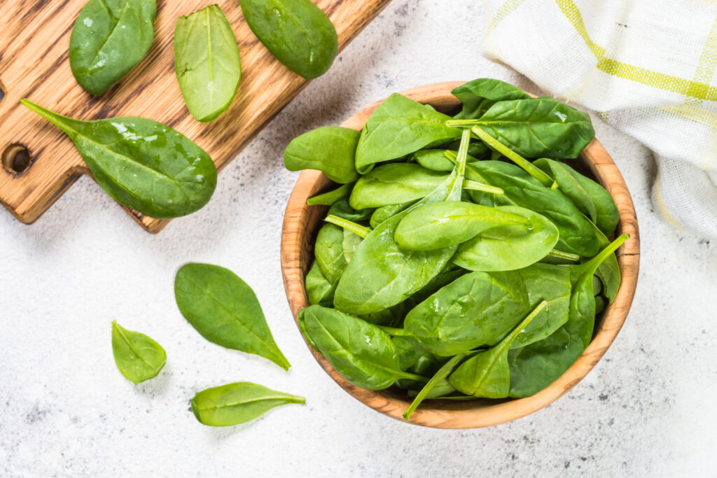 Baby spinach leaves in wooden bowl on white background. Top view.
